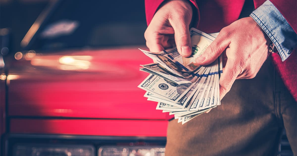Man counting american money in front of a red vintage car