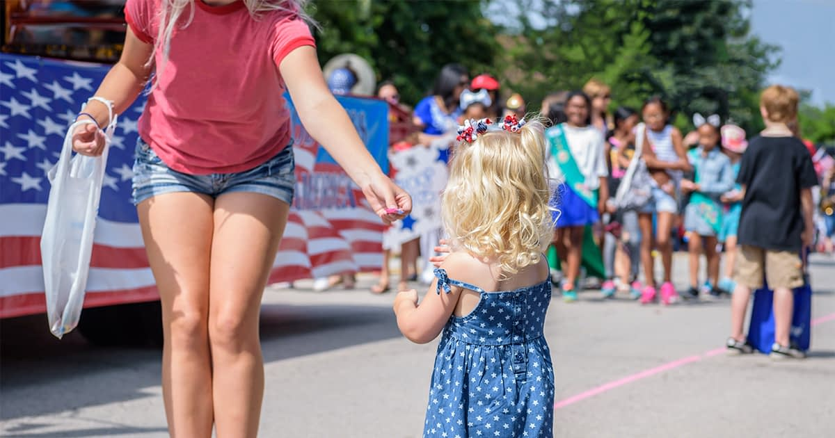 woman and child in front of a 4th of july parade float