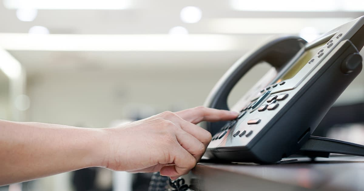 finger dialing a desk phone