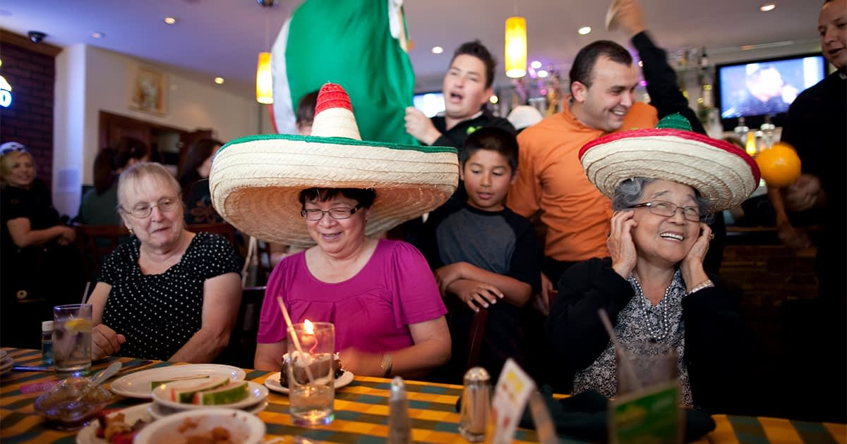 Family eating Mexican food in sombreros.