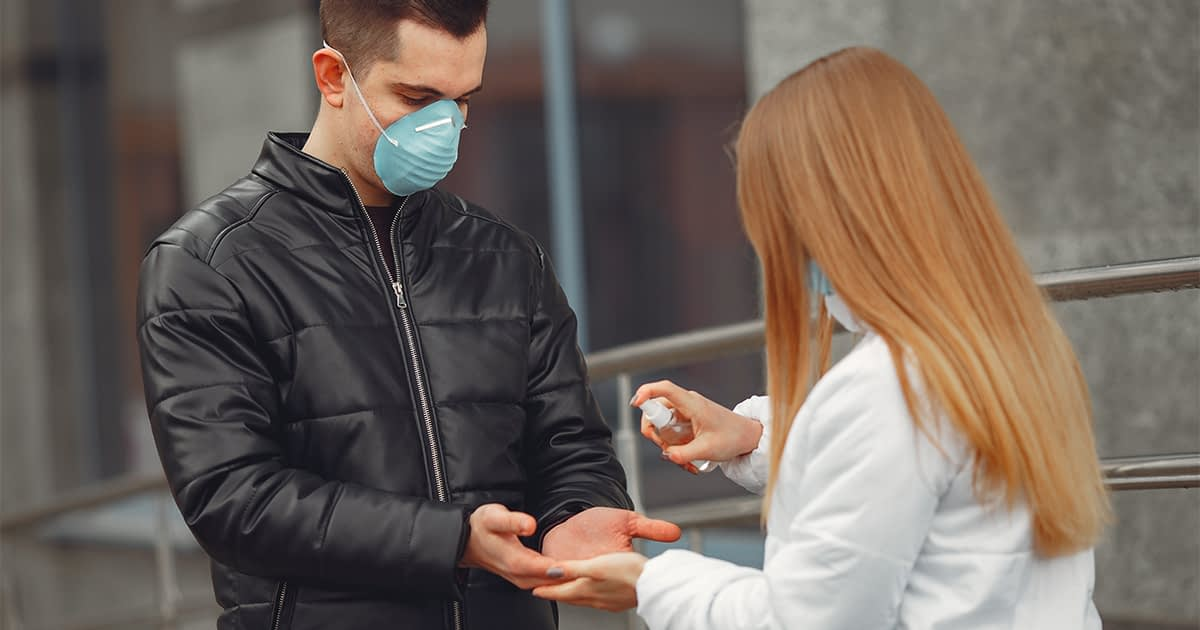 Woman giving hand sanitizer to friend in public