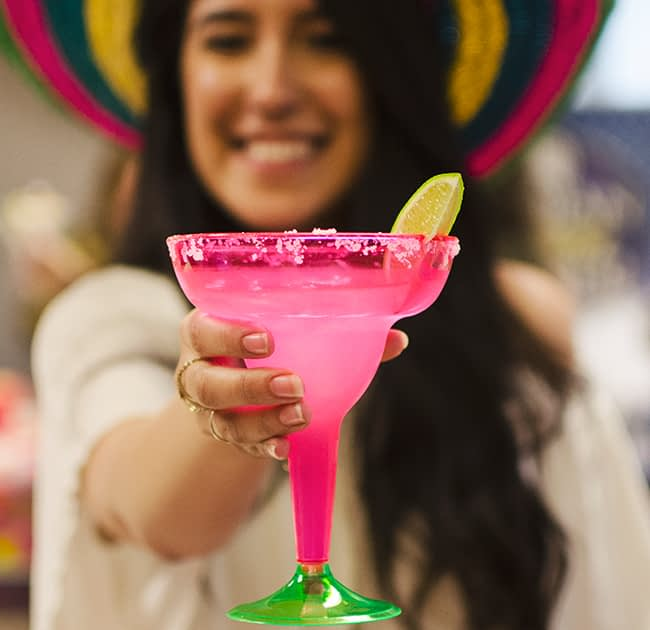 Woman holding a margarita in a sombrero on cinco de mayo