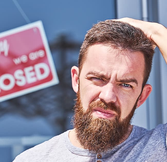 A man in distress standing in front of a closed business sign