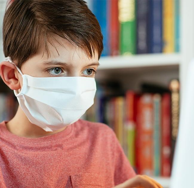 boy wearing a mask in class