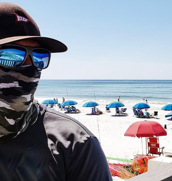 Man wearing a bandana face cloth at the beach in california during Covid-19