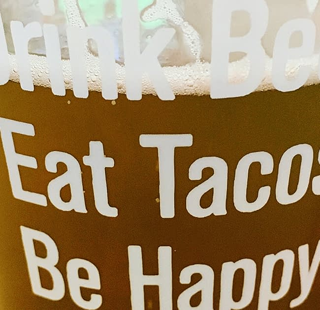 beer in a glass that has print on it saying 'Drink beer. eat tacos. be happy. '