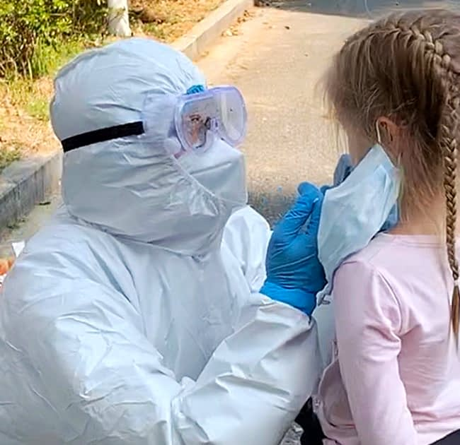 Hazmat doctor diagnosing masked child